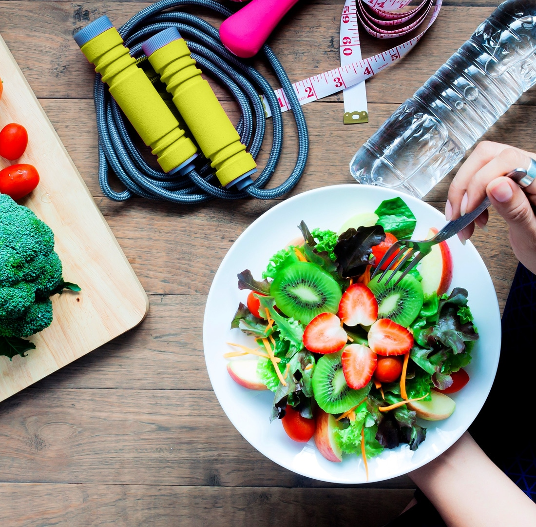 Someone holding a salad and jump-rope on the table showing the Benefits of Good Nutrition
