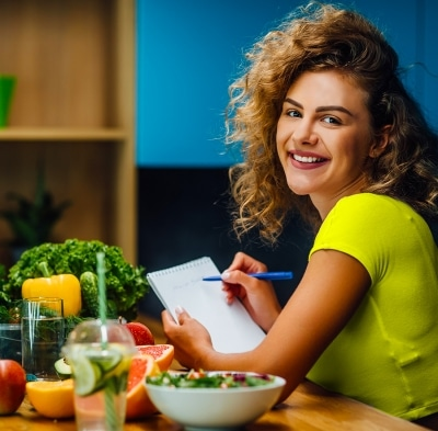 Eat Healthy | Woman in green shirt with fruit and vegetables around her
