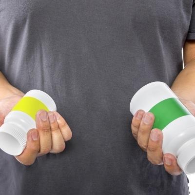Guy holding two pill bottles