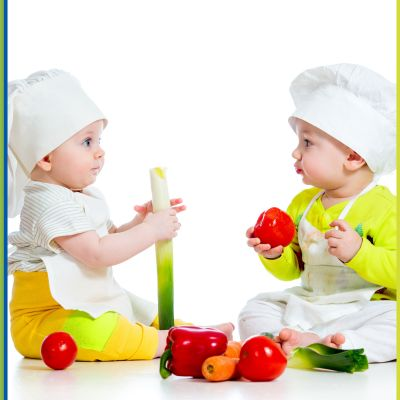 Two babies playing with vegetables