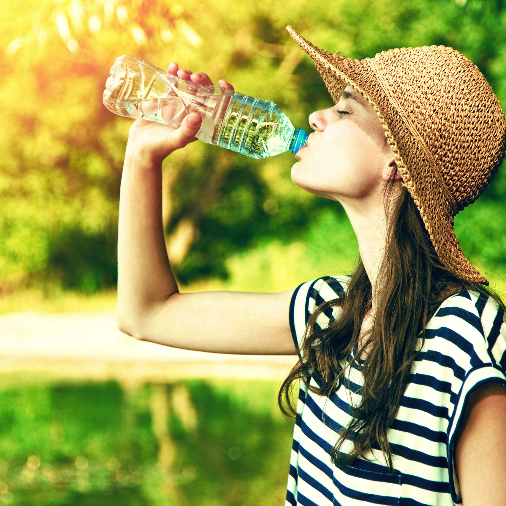 Woman drinking water in the summer heat.