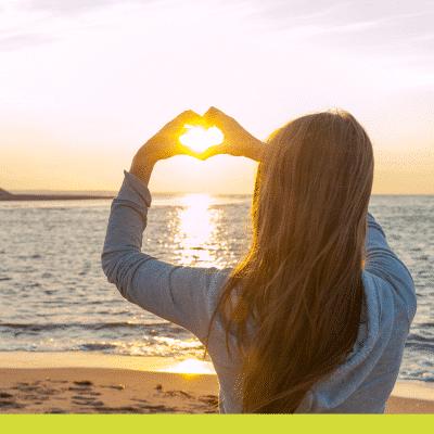 Woman making a Heart shape with her hands to the sun