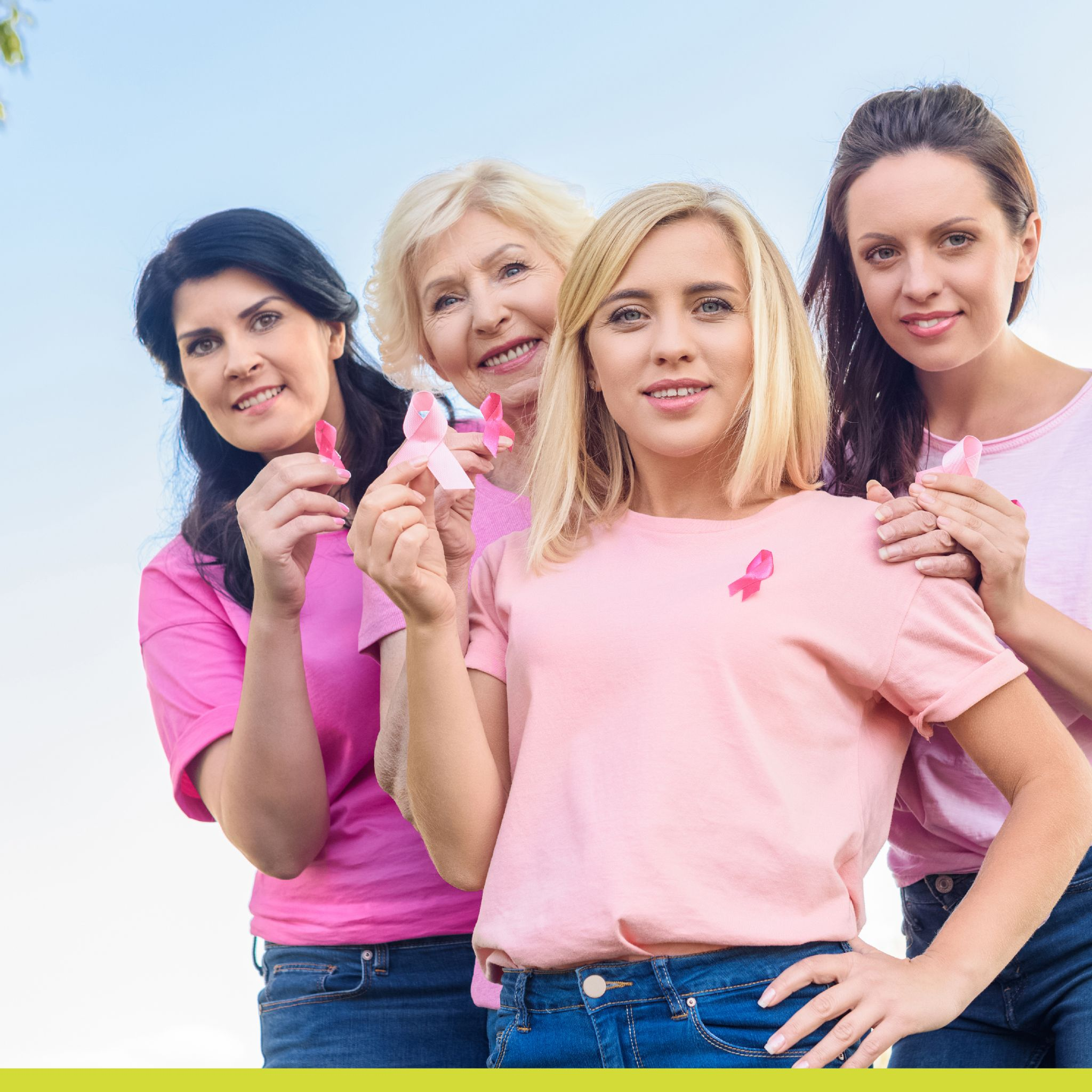 Women in pink shirts holding Breast Cancer awareness ribbons